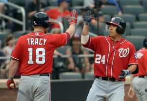 Washington Nationals catcher Kurt Suzuki (24) high fives first baseman Chad Tracy (18) after his two-run home run in the 8th inning against the New York Mets at Citi Field. Mandatory Credit: Robert Deutsch-USA TODAY Sports