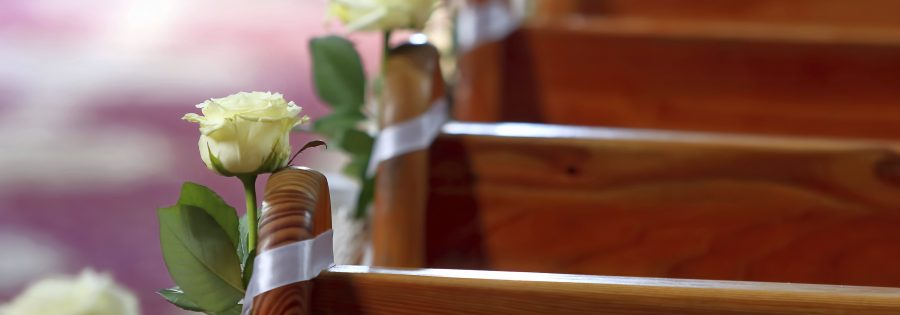 Decoration on the benches in the church before wedding ceremony
