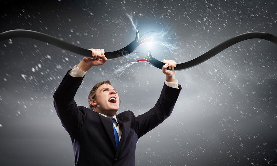 Young businessman tearing electricity cable with hands