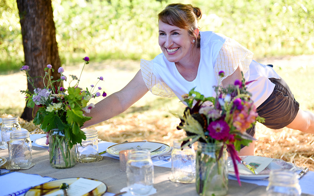 Lisa places flowers on a table.