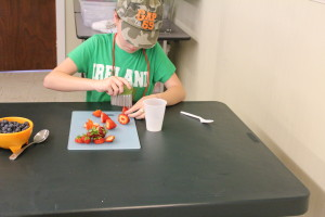 A Red Pepper helps prepare the strawberries for their parfaits