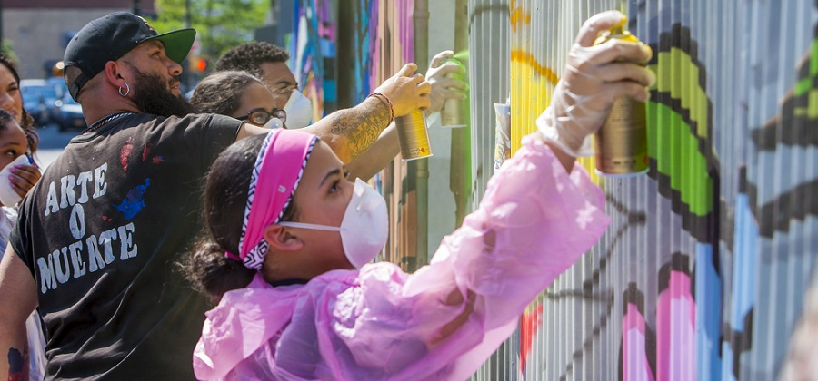 Participants spray paint a mural as part of WHEDco's ArtsFest.