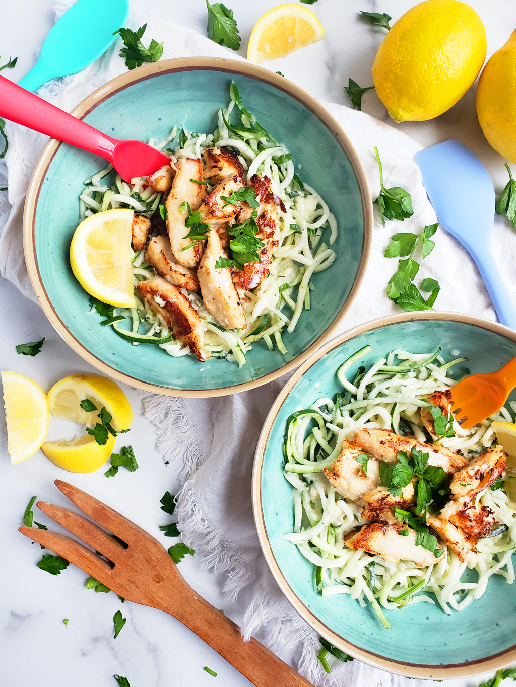 Creamy Lemony Chicken & Zoodles in a blue bowl with zucchini noodles, parsley and lemon slices. Perfect for kids.