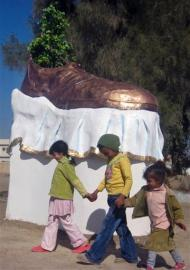 Girls stand next to a sculpture of a shoe that serves as a monument to the shoes thrown at then-US president George W. Bush in Tikrit