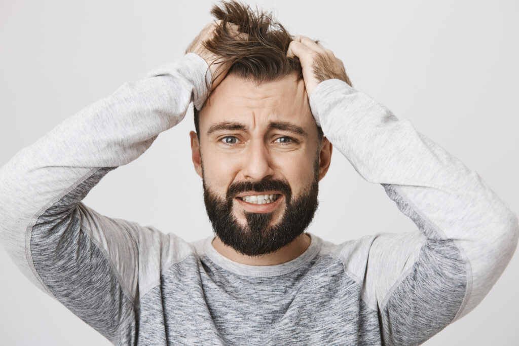 Portrait of depressed bearded guy feeling pressure, grabbing hair with hands and expressing devastation, standing over gray background. Huge grief just happened and man feels broken. Emotions concept