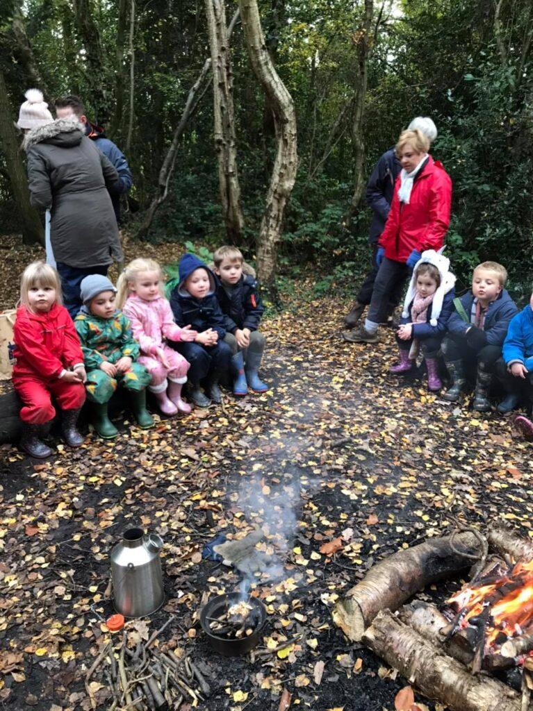 The children sitting around the fire