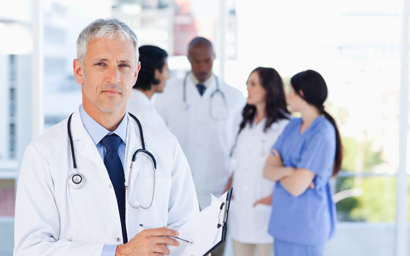 One doctor standing apart from four other doctors discussing information.