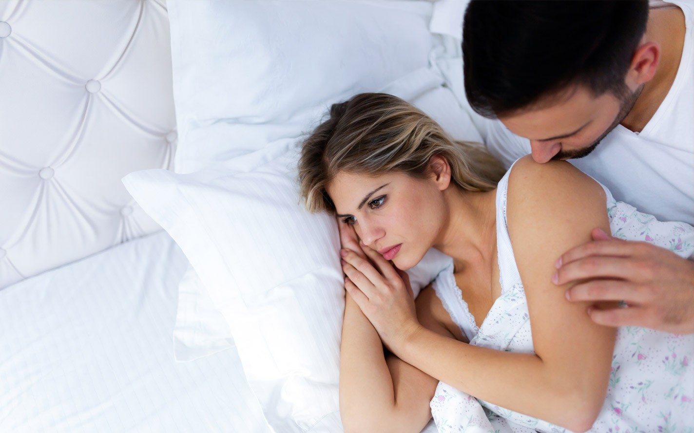 Disappointed woman looking away from her husband with erectile dysfunction.