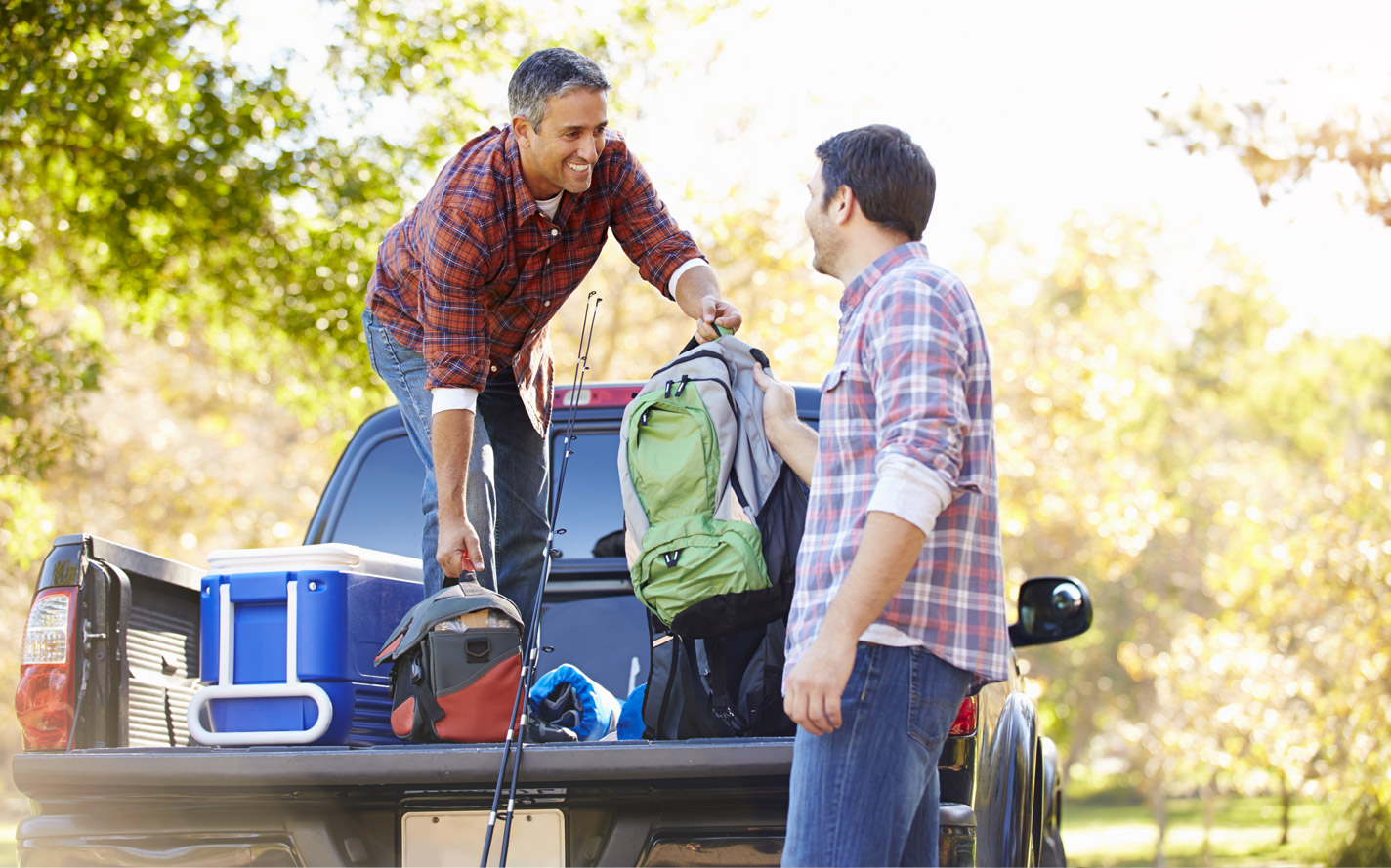 Two guys unloading a truck with fishing gear.