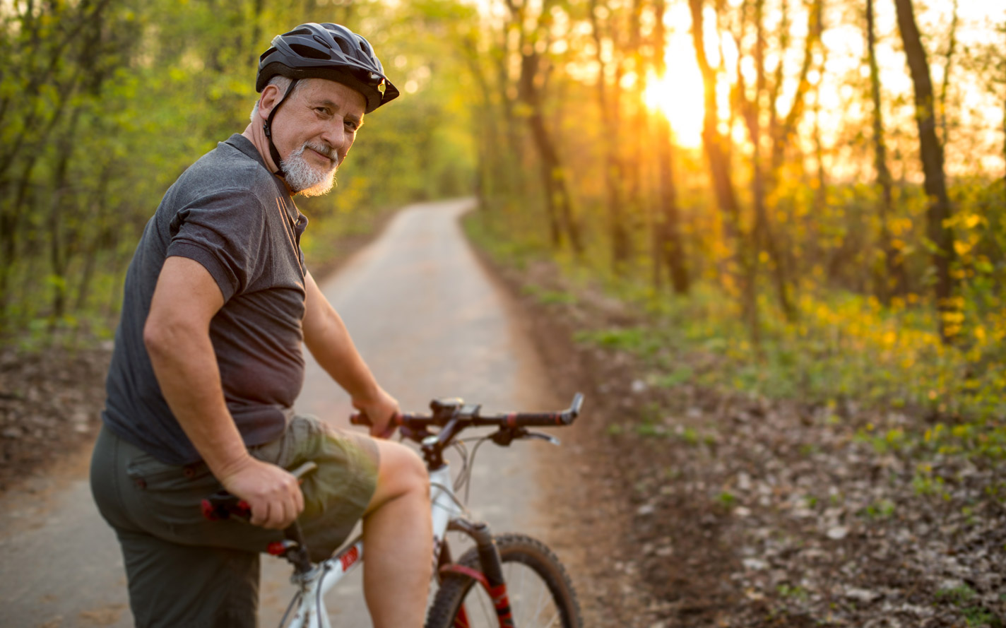 Older man riding a bicycle down the road.