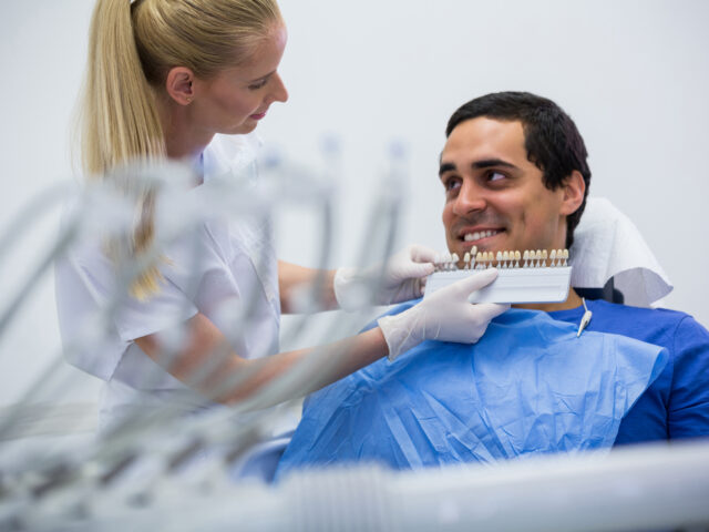 Dentist examining female patient with teeth shades at clinic