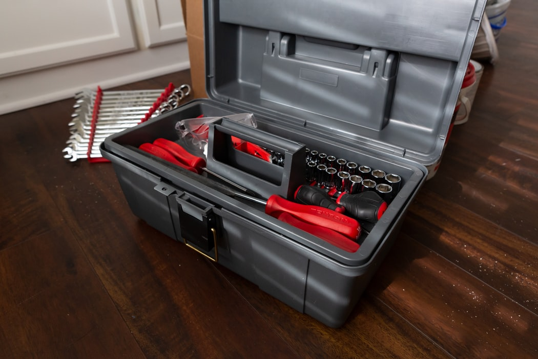 A grey toolbox packed with tools