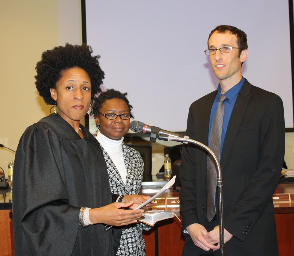 Municipal Court Judge June Hardwick swears in JPS board member Jed Oppenheim as his fiancée Harriett Johnson looks on. PHOTO BY AYESHA K. MUSTAFAA