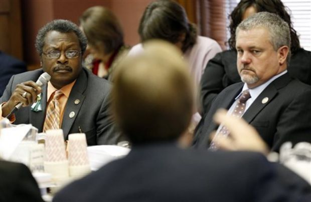 House Education Committee Chairman John Moore, R-Brandon, with back to camera, explains elements of his Teacher Pay Raise legislation to House Appropriations Committee members Charles Busby, R-Pascagoula, right, and Willie Perkins, D-Greenwood., Tuesday, Feb. 4, 2014 at the Capitol in Jackson, Miss. Lawmakers were facing a deadline for their committees to report general bills originating in their own chamber. (AP Photo/Rogelio V. Solis)