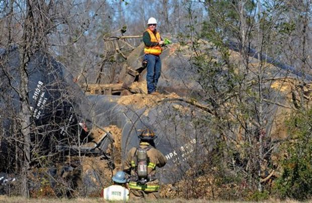 Emergency crews work the scene of a Canadian National Railway train derailment along U.S. 98, West of New Augusta Miss., on Friday, Jan. 31, 2014. A train derailment Friday in southeast Mississippi sparked a small evacuation and highway closure after rail cars began leaking fuel oil. (AP Photo/Hattiesburg American, Ryan Moore)