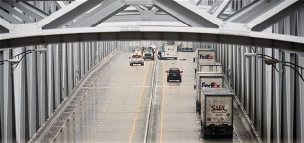 A row of 18-wheelers, right, sits idle in the west-bound lanes of Interstate 20 over the Mississippi River Bridge as emergency vehicles work to clear the scene of an early-morning accident involving an 18-wheeler transporting a hazardous material near Vicksburg, Miss., Wednesday, Feb. 12, 2014. An undetermined amount of the chemical is believed to have leaked into the Mississippi River, officials said. U.S. Coast Guard officials said they were assessing the impact of the spill Wednesday. (AP Photo/The Clarion-Ledger, Joe Ellis)