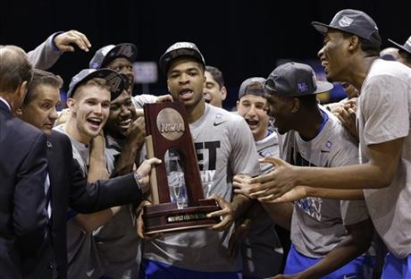 Kentucky's Aaron Harrison and his teammates hold up their trophy after an NCAA Midwest Regional final college basketball tournament game against Michigan Sunday, March 30, 2014, in Indianapolis. Kentucky won 75-72 to advance to the Final Four. (AP Photo/David J. Phillip)