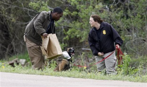 """""""Buddy,"""" the scent dog for the Mississippi Fire Marshal's Office is offered a sniff of a particle of clothing belonging to a 9-year-old girl who authorities say is believed to have been swept away by flash flood waters along a Yazoo City, Miss., culvert, Monday, April 7, 2014. The dog was one of a number of participants in the search of the child who authorities say is believed to have been swept away by flash flood waters on Sunday. Yazoo County Director of Emergency Management Joey Ward said emergency crews, a dive team and volunteers searched rain-swollen drainage ditches until about midnight and resumed Monday. (AP Photo/Rogelio V. Solis)"""