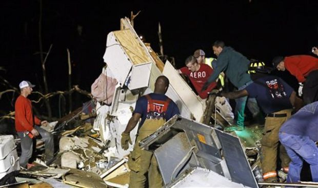 Emergency personnel search the remains of several mobile homes in Louisville, Miss., for survivors early Tuesday morning, April 29, 2014 after a tornado hit the east Mississippi community Monday. Tornadoes flattened homes and businesses, flipped trucks over on highways and bent telephone poles into 45-degree angles as they barreled through Alabama and Mississippi on Monday. (AP Photo/Rogelio V. Solis)