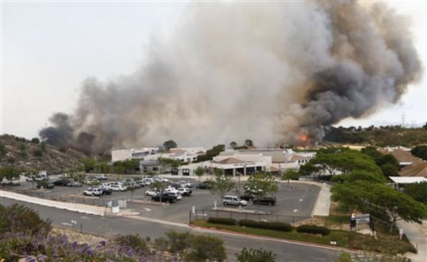 wild fire burns toward a Aviara Oaks Middle School Wednesday, May 14, 2014, in Carlsbad, Calif. Wind-driven flames are threatening homes in the coastal city of Carlsbad, where officials have sent mandatory evacuation notices to more than 11,000 homes and businesses. (AP Photo)