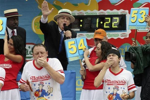 Joey Chestnut, left, and Matt Stonie, right, compete at the Nathan's Famous Fourth of July International Hot Dog Eating contest at Coney Island, Friday, July 4, 2014, in New York. Reigning champion Chestnut won his eighth contest by finishing 61 hot dogs and buns. (AP Photo/John Minchillo)