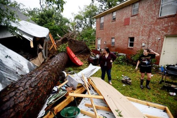 Brittany Garner, right, shows Toshia Laing the tree that fell in her backyard during the storm Monday, Oct. 13, 2014, in Monroe, La. (AP Photo/The Shreveport Times, Henrietta Wildsmith)