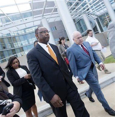 Former Mississippi Corrections Commissioner Chris Epps, center, and his attorney John Colette, right, leave the federal courthouse after an arraignment hearing in Jackson Thursday. Epps, who resigned abruptly this week, has been charged with accepting hundreds of thousands of dollars in bribes from a Rankin County businessman connected to several private prison companies. Thursday afternoon, Gov. Phil Bryant announced all contracts involving firms mentioned in the Epps indictment will be rebid. The Associated Press/Joe Ellis