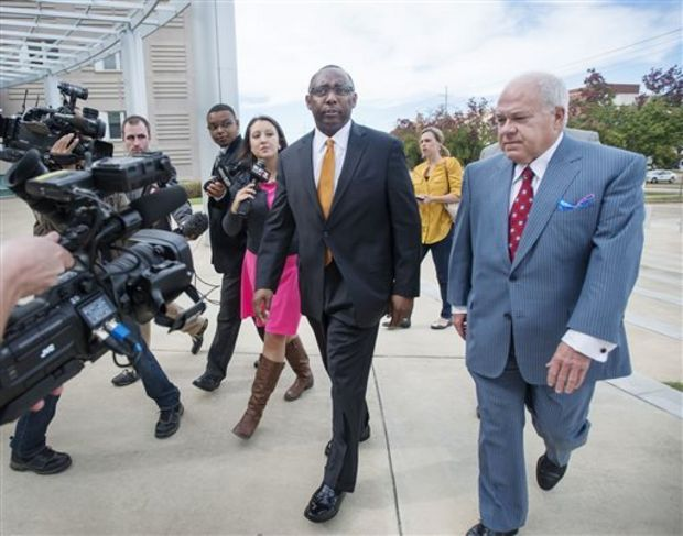 Former Mississippi Corrections Commissioner Chris Epps, center, and his attorney John Colette, right, arrive at the federal courthouse in Jackson, Miss., Thursday, Nov. 6, 2014. Epps, who resigned abruptly this week, has been charged with accepting hundreds of thousands of dollars in bribes from a Rankin County businessman connected to several private prison companies. (AP Photo/The Clarion-Ledger, Joe Ellis)