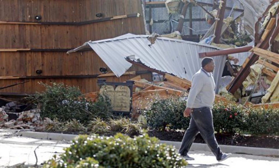 A resident walks past a Ten Commandments display in Columbia, Miss., Wednesday, Dec. 24, 2014. The community was hit by a storm that destroyed several businesses and homes and killed at least four people. (AP Photo/Rogelio V. Solis)