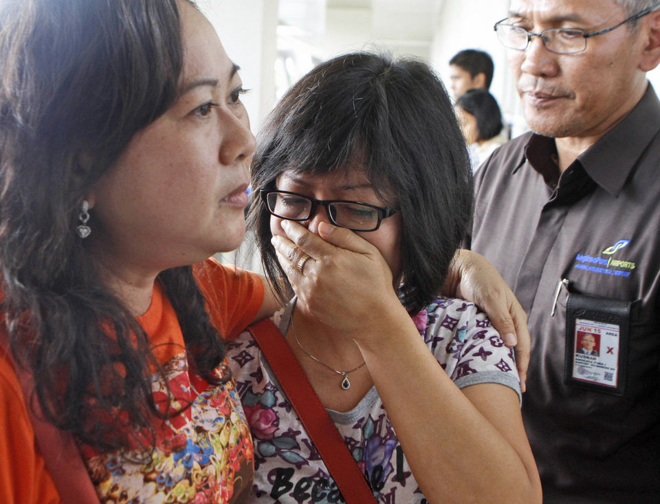 A relative of Air Asia flight QZ8501 passengers weep as she waits for the latest news on the missing jetliner at Juanda International Airport in Surabaya, East Java, Indonesia, Sunday, Dec. 28, 2014. The AirAsia plane with 161 people on board lost contact with ground control on Sunday while flying over the Java Sea after taking off from the provincial city in Indonesia for Singapore. (AP Photo/Trisnadi)