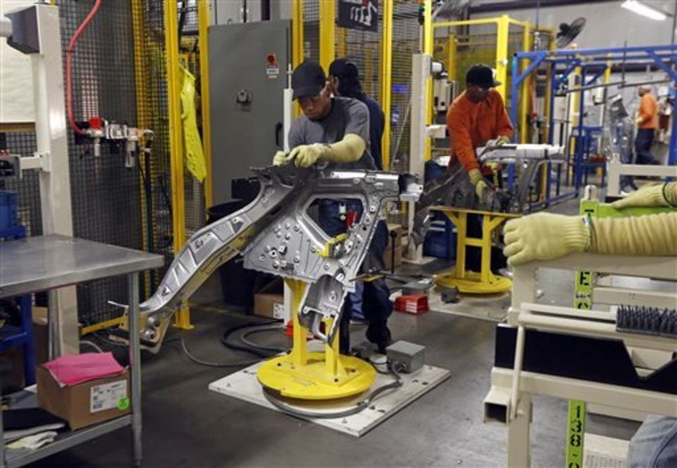 In this Dec. 12, 2014 photograph, a Topre America worker adjusts a support frame for welding by one of the company's robots in Canton, Miss. Japanese-based Topre is one of seven suppliers expanding or setting up operations on Nissan's 1.5-million-square-foot integrated logistics center, as the automaker focuses on improving its parts supply as it works to increase production capacity at its Mississippi plant. (AP Photo/Rogelio V. Solis)