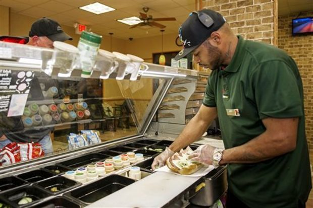 In a Wednesday, Dec. 17, 2014 photo, Michael Ellington makes a sandwich for a customer, at Subway near the Lincoln Airport in Lincoln, Neb. Ellington, an inmate at the Community Corrections Center of Lincoln who served nearly seven years for robbery, is nearing parole at the end of the year. He says he is grateful for his time at the Community Corrections Center in Lincoln. (AP Photo/The Journal-Star, Kristin Streff)