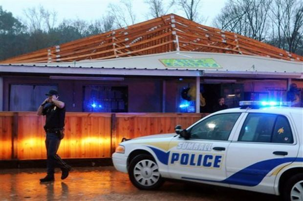 Police inspect Kid's Kampus, a daycare facility after a tornado ripped the roof off of the building in Sumrall, Miss., Tuesday, Dec. 23, 2014. According to the Sumrall Police Department, all 30 children and employees were unharmed and moved to the neighboring Citizens Bank. (AP Photo/The Hattiesburg American, Eli Baylis)