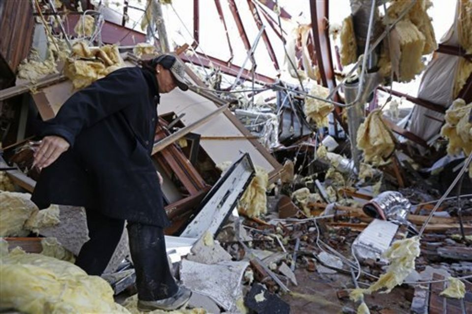 Sandra McDaniel walks through the remains of the product showroom for Jack Morris Gas Company in Columbia, Miss., Wednesday, Dec. 24, 2014. The community was hard hit by a tornado on Tuesday that destroyed several businesses and homes and have two deaths attributed directly to it. (AP Photo/Rogelio V. Solis)