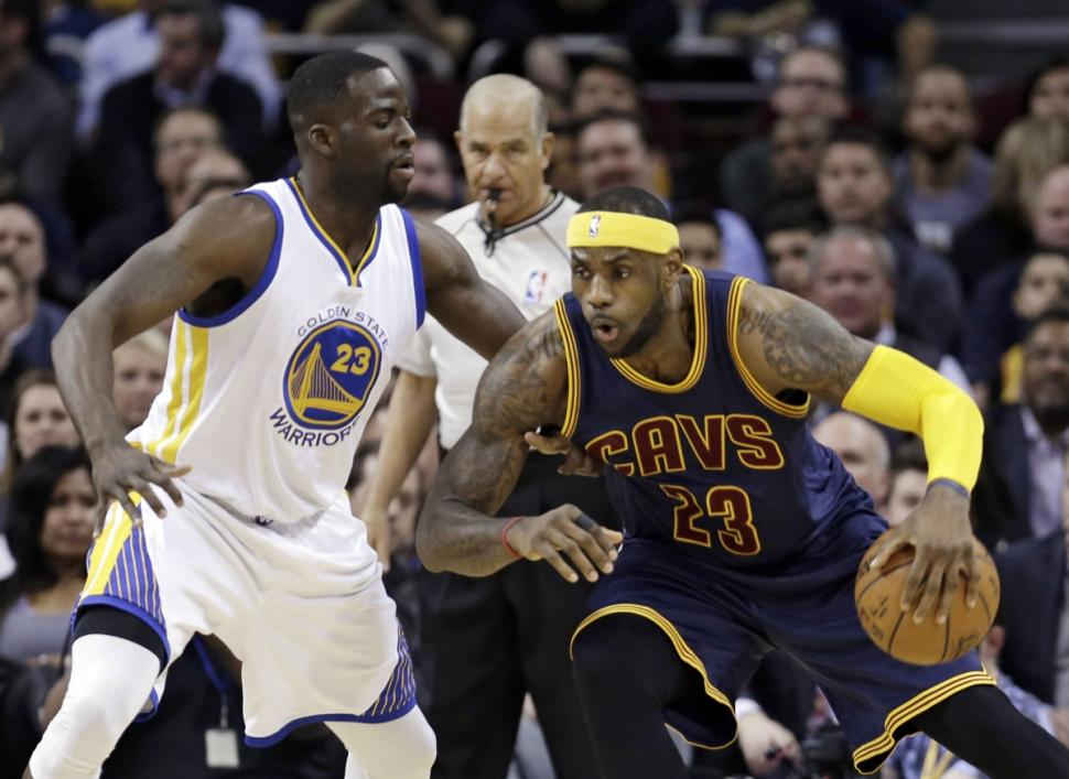 Cleveland's LeBron James (r.) works on Warriors forward Draymond Green in the first quarter of his 42-point effort that boosts the Cavs to a victory.
