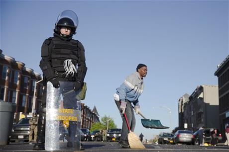 Residents clean streets as law enforcement officers stand guard, Tuesday, April 28, 2015, in Baltimore, in the aftermath of rioting following Monday\'s funeral of Freddie Gray, who died in police custody. (AP Photo/Matt Rourke)