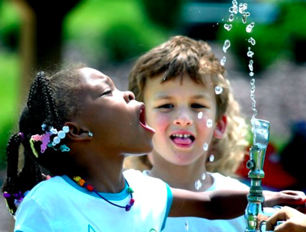 In this June 3, 2008 file photo, Tianna Swisher, a student at Liberty Valley Elementary School in Danville, Pa., attempts to drink from the water fountain at Montour Preserve near Washingtonville, Pa., during an outdoor field trip. Fluoride in drinking water, credited with dramatically cutting cavities and tooth decay, may now be too much of a good thing. It's causing spots on some kids' teeth. The federal government announced Monday, April 27, 2015, that it is lowering the recommended level of fluoride in drinking water for the first time in more than 50 years. (AP)