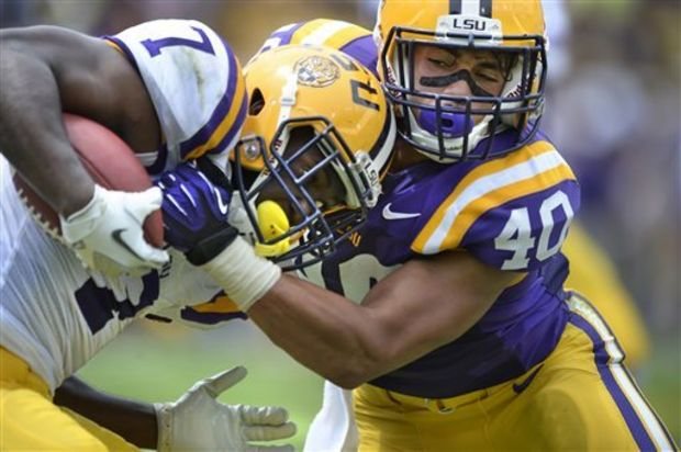 LSU running back Leonard Fournette, left, is stopped for a 5-yard loss on a swing pass, on a hit from linebacker Duke Riley (40) during the NCAA college football team's spring football game Saturday, April 18, 2015, in Baton Rouge, La. (Travis Spradling/The Baton Rouge Advocate via AP)