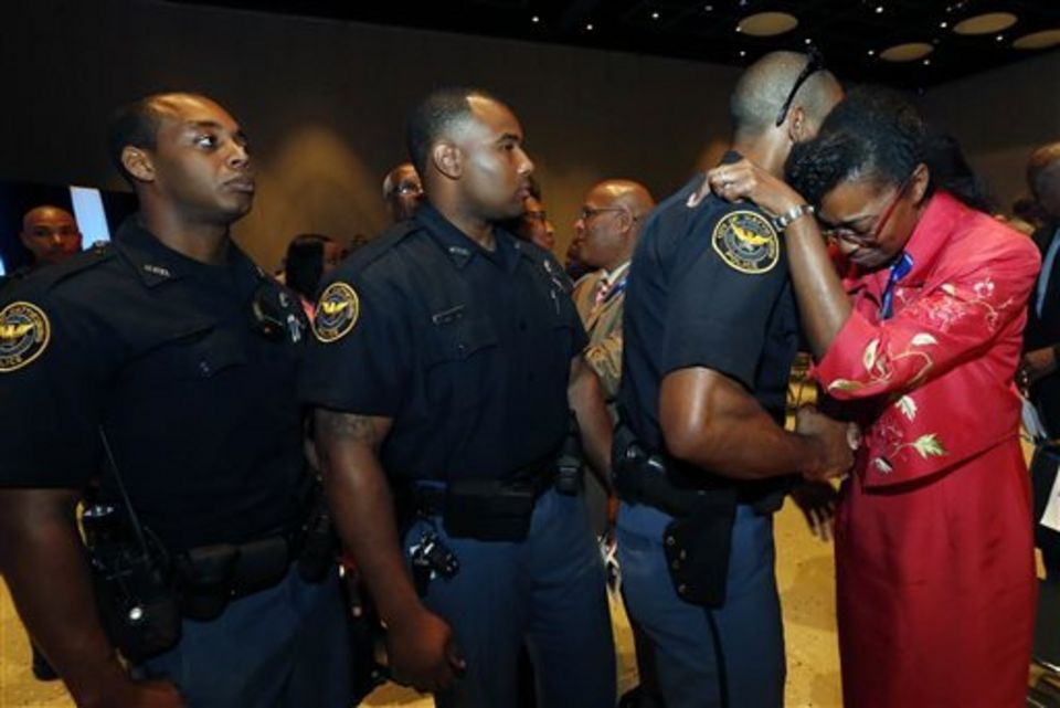 Youlander Ross, right, mother of slain Hattiesburg Police Officer Liquori Tate, is embraced by an officer after a vigil service Monday, May 11, 2015, in Hattiesburg, Miss. Marvin Banks faces two counts of capital murder in the Saturday shootings of Officers Benjamin Deen and Tate following a traffic stop. (AP Photo/Rogelio V. Solis)