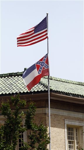 The state flag of Mississippi is unfurled underneath the American flag at the Secretary of State's Office building in downtown Jackson, Miss., Tuesday, June 23, 2015. Republican Lt. Gov. Tate Reeves said Tuesday, that Mississippi voters, not lawmakers, should decide whether to remove the Confederate battle emblem from the state flag. Reeves, who presides over the state Senate, spoke about the issue a day after Republican House Speaker Philip Gunn called the emblem offensive and said the state flag should change. (AP Photo/Rogelio V. Solis