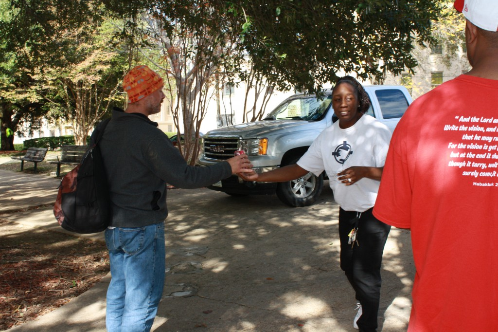 LaKeshia Robinson gives a soda to a man in need.