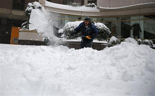 Alfredo Milian shovels a walkway in downtown Washington, D.C., Saturday, Jan. 23, 2016. (Gerald Herbert/The Associated Press)