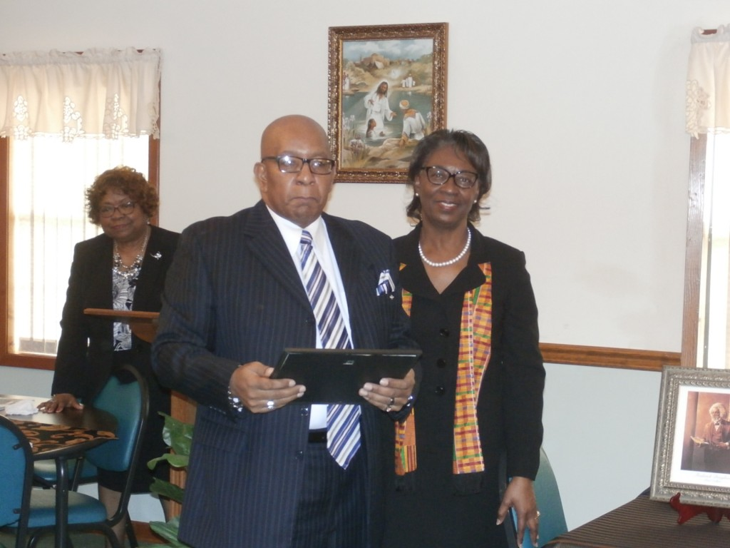 Club member Ernestine Bridges presents Joephuse Laird, owner of Laird Mortuary, a certificate of appreciation.