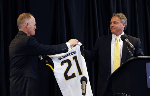 Southern Mississippi football coach Jay Hopson, right, is presented with a football jersey with the No. 21, signifying his being the school's 21st football coach, by athletic director Bill McGillis moments after being introduced to gathered fans, reporters and alumni, Monday, Feb. 1, 2016, in Hattiesburg, Miss. Hopson was hired from Alcorn State, where he led the Braves to back-to-back Southwestern Athletic Conference championships. (Rogelio V. Solis/The Associated Press)