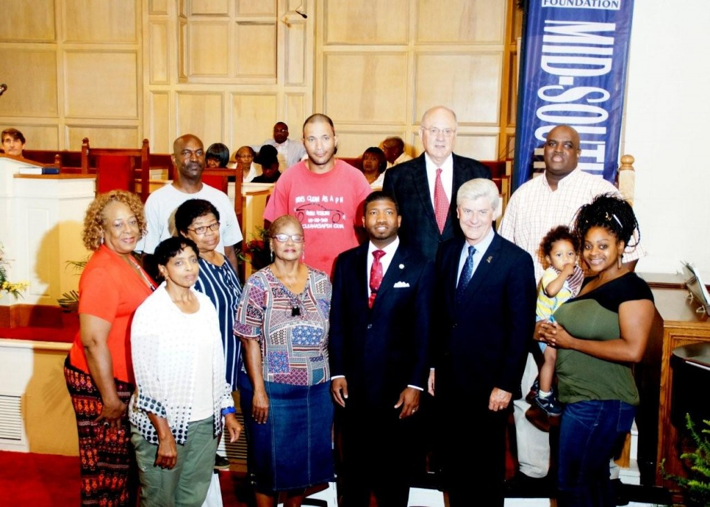 Helm Place residents stand with Rev. C.J. Rhodes (center), Gov. Phil Bryant (right) and Clarence Chapman of Chartre Consulting (back row with tie). PHOTO BY JAY JOHNSON