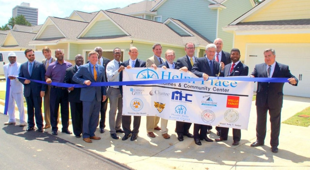 Rev. C.J. Rhodes, pastor of Mount Helm Baptist Church, and Gov. Phil Bryant cut the ribbon for the official opening of Helm Place July 14, in downtown Jackson. Standing with them are several local and national dignitaries involved in the development.  PHOTO BY JAY JOHNSON