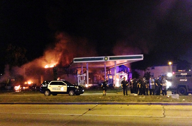 Authorities respond near a burning gas station as dozens of people protest following the fatal shooting of a man in Milwaukee, Saturday, Aug. 13, 2016. (AP Photo/Gretchen Ehlke)
