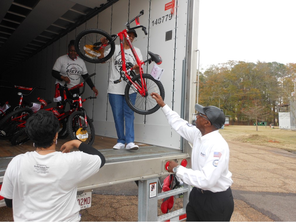 Carolyn Warner and other volunteers help Walmart manager Billy Tingle unload bikes.
