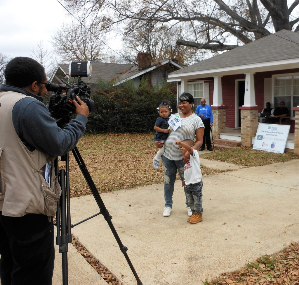 Lequoya Williams and her children, Riyah and Syrius, pose for cameras Monday in front of their new Habitat home.