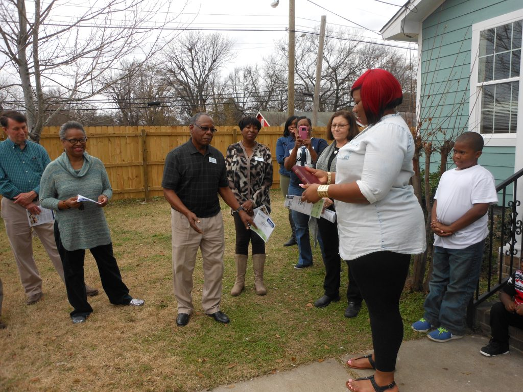 Habitat for Humanity board member Johnny Anthony presents a Bible to new homeowner Tierra Christian on Kevin Garnett St.